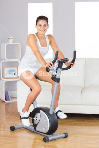 Cheerful young woman training on an exercise bike in her living room
