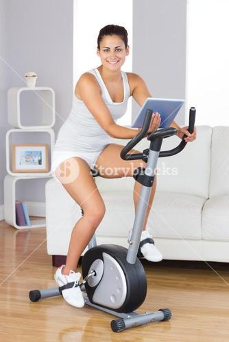 Happy training woman using an exercise bike while holding a tablet