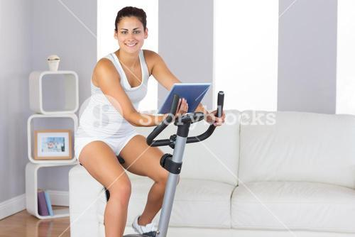 Cheerful sporty woman training on an exercise bike while holding a tablet