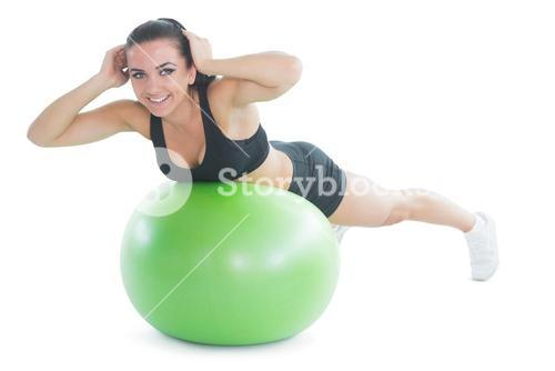 Happy fit woman doing an exercise on a green fitnessball