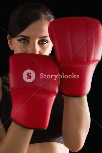 Front view of young sporty woman posing wearing boxing gloves