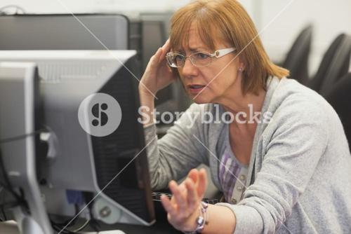 Angry mature student working with computer