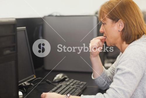 Unsure female mature student working on computer