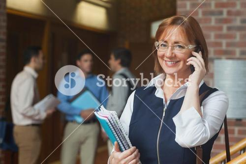 Cheerful mature student phoning with her smartphone
