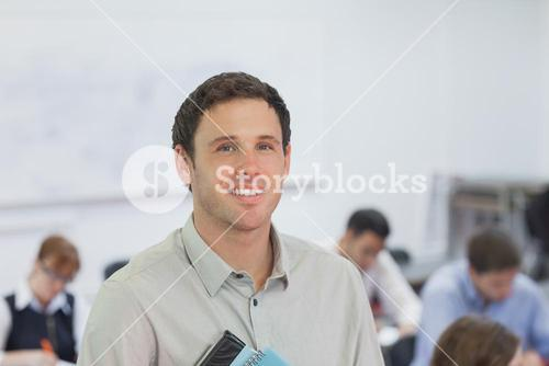 Cute male teacher standing in his classroom