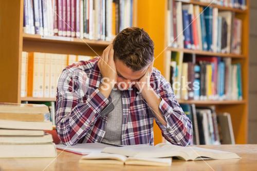 Handsome frustrated student studying his books