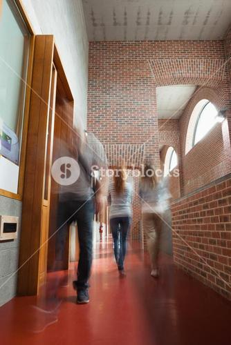 Students walking through hallway away from camera