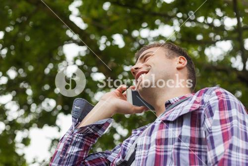 Handsome laughing student standing and phoning