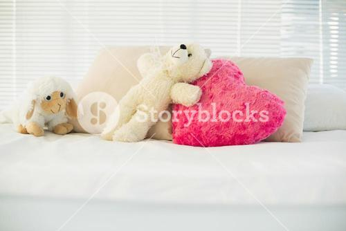 Stuffed animals and a heart pillow lying on couch