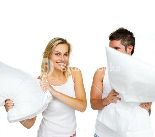 Nice couple fighting with pillows