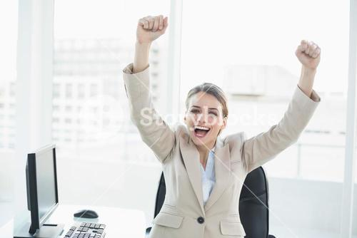 Happy cheering woman raising her arms sitting on her swivel chair