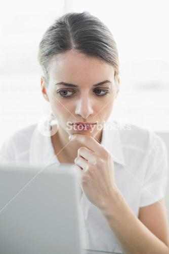 Beautiful businesswoman sitting concentrating at her desk