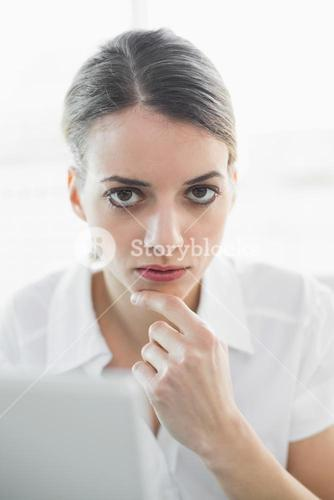 Calm thoughtful businesswoman looking at camera