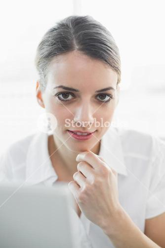 Content thinking businesswoman smiling softly at camera