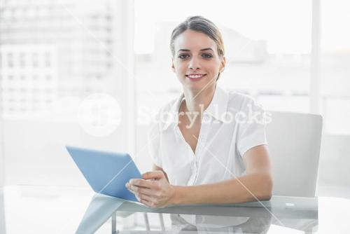 Gleeful smiling businesswoman working with her tablet looking at camera