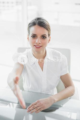 Friendly young businesswoman reaching her hand to camera