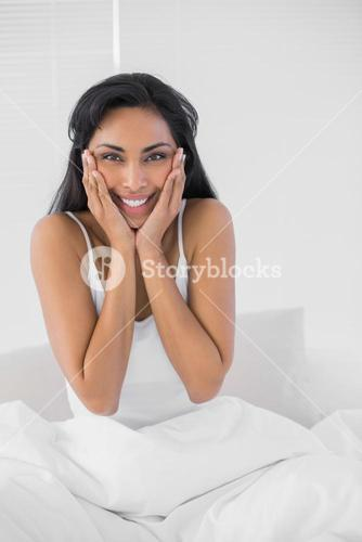 Gleeful dark haired woman posing smiling at camera