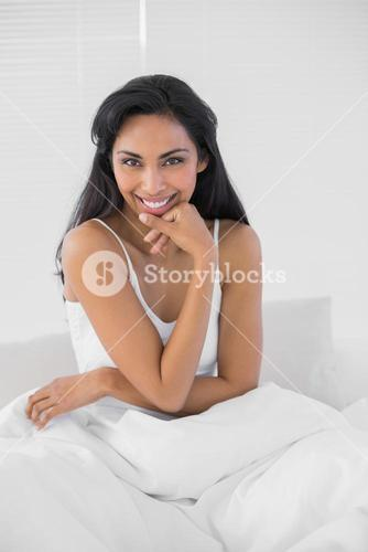 Lovely dark haired woman posing while sitting on her bed
