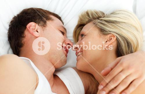 Lovers looking each other in bed