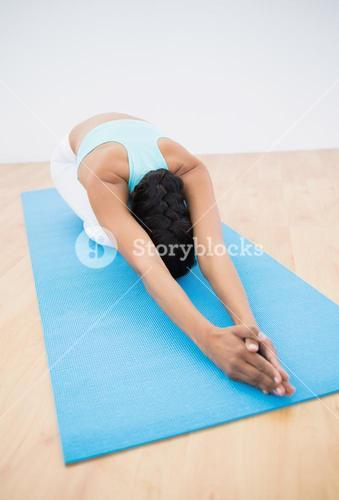 Slender darkhaired woman stretching on blue exercise mat