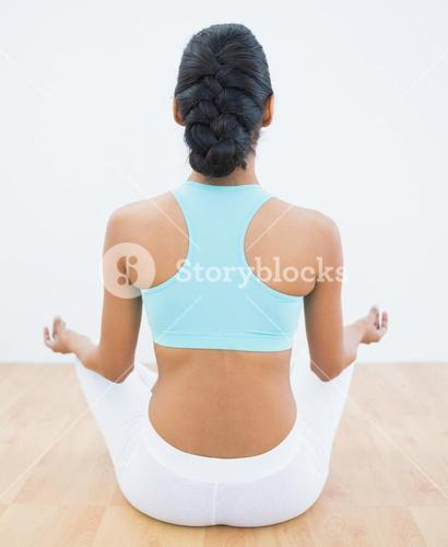 Rear view of slender calm woman meditating in lotus position