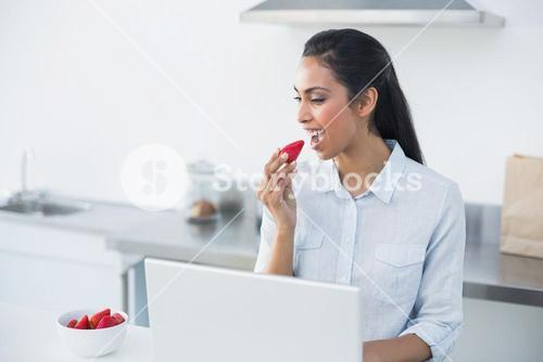 Peaceful dark haired woman eating strawberry