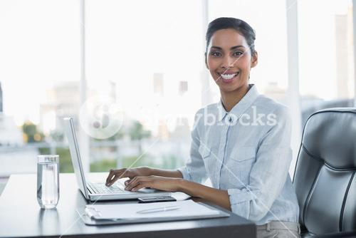 Cheerful smiling businesswoman working on her laptop