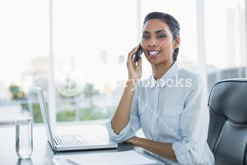 Young black haired businesswoman sitting at her desk
