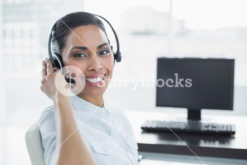 Smiling female agent wearing a headset sitting in bright office
