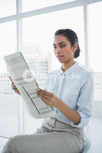 Softly smiling chic businesswoman reading newspaper