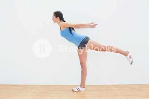 Full length of a woman standing on one leg in fitness center
