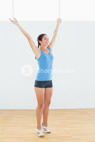 Happy woman in sportswear with raised hands