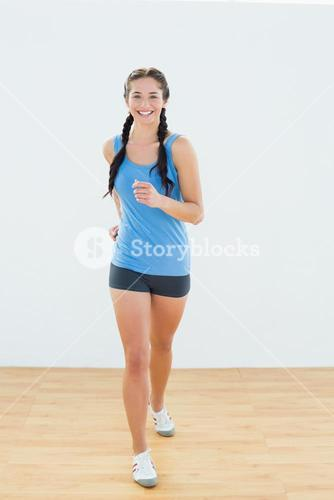 Portrait of a sporty woman in jogging posture at fitness center