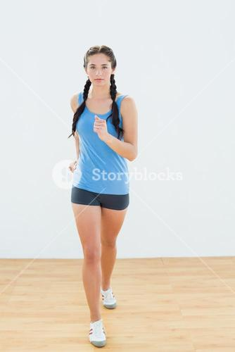 Sporty woman in jogging posture at fitness center