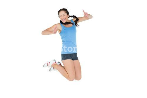 Sporty young woman jumping mid air