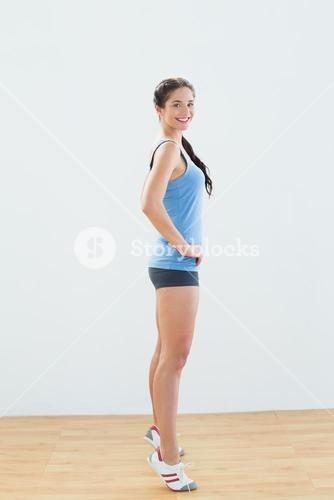 Side view of a sporty woman tip toeing