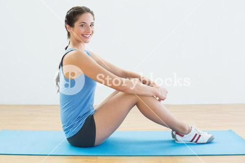 Portrait of a fit woman sitting upright on exercise mat