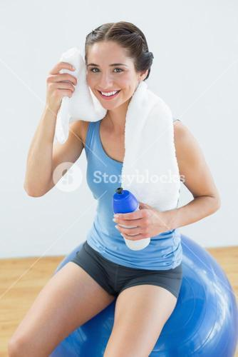 Woman with towel around neck and waterbottle sitting on exercise ball