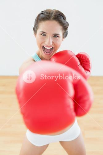 Beautiful playful woman in red boxing gloves at fitness studio