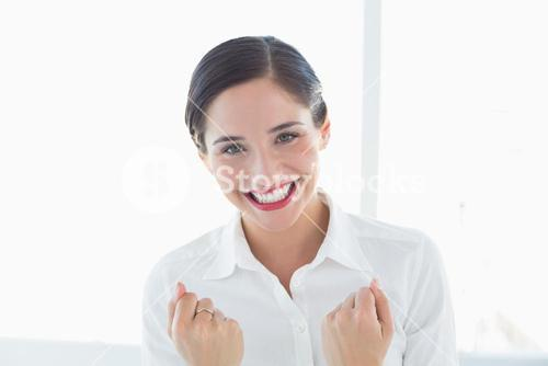 Excited young business woman clenched fists