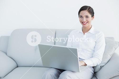 Smiling well dressed young woman using laptop on sofa