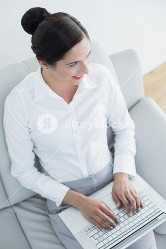 Well dressed young woman using laptop on sofa