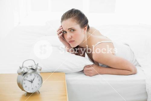 Displeased woman in bed with alarm clock in foreground