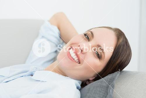 Close up portrait of a smiling well dressed woman relaxing on sofa