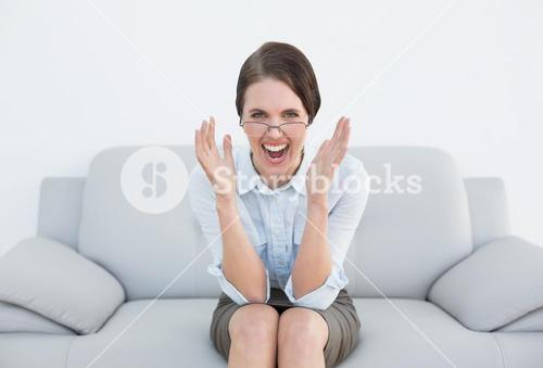 Displeased well dressed woman screaming on sofa