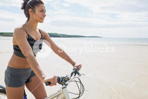 Content young woman riding her bike on the beach