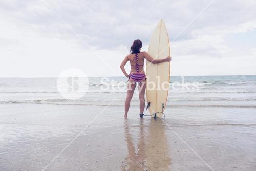Woman in bikini with surfboard on beach