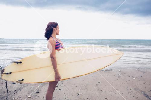 Woman carrying surfboard on the beach