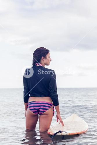 Rear view of a woman with surfboard in water