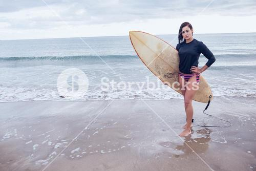 Full length of a woman with surfboard at beach